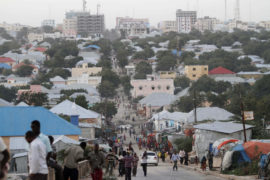 People walk along a street in Mogadishu September 28, 2013. Street lamps now brighten some of Mogadishu's battle-scarred roads and couples hold hands at the seaside next to bombed-out beachfront buildings, a scene that would have been unthinkable when the Islamist al Shabaab group held sway here. However, rebuilding a life many in the world take for granted is a slow process after more than 20 years of civil war and anarchy in Somalia. Islamists, who control swathes of countryside and some towns, have launched several attacks in Mogadishu, and last month they showed their reach, claiming responsibility for a deadly attack on a Kenyan shopping mall. Picture taken September 28, 2013. REUTERS/Feisal Omar (SOMALIA - Tags: CONFLICT POLITICS SOCIETY)  ATTENTION EDITORS: PICTURE 01 OF 48 FOR PACKAGE  'DAILY LIFE IN MOGADISHU'  SEARCH 'MOGADISHU BEACHFRONT' FOR ALL IMAGES - RTX14EVJ