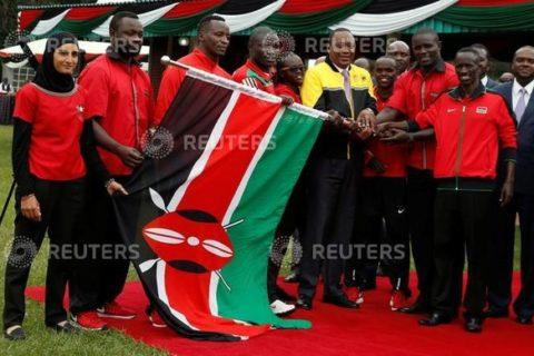Kenyan President Uhuru Kenyatta (C) hands over the national flag to members of the Kenyan Olympics team from different sports disciplines at the State House in Nairobi, Kenya, July 22, 2016. REUTERS/Thomas Mukoya