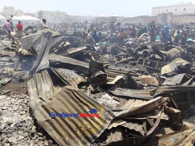 Traders comb through the remains of property by fire in Bakaaro market Monday. Photo: Abdinajib Dahi Goobjoog Business