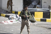 "Houthi Shiite Yemeni wearing an army uniform stand guard in front of a building damaged during recent clashes near the presidential palace in Sanaa, Yemen, Tuesday, Jan. 20, 2015. Yemen's U.S.-backed leadership came under serious threat Monday as government troops clashed with Shiite rebels near the presidential palace and a key military base in what one official called ""a step toward a coup."" (AP Photo/Hani Mohammed)"