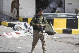 """Houthi Shiite Yemeni wearing an army uniform stand guard in front of a building damaged during recent clashes near the presidential palace in Sanaa, Yemen, Tuesday, Jan. 20, 2015. Yemen's U.S.-backed leadership came under serious threat Monday as government troops clashed with Shiite rebels near the presidential palace and a key military base in what one official called """"a step toward a coup."""" (AP Photo/Hani Mohammed)"""