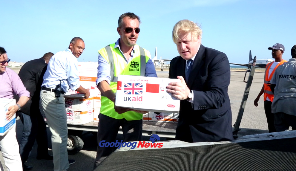 UK Foreign Secretary loading cartoons of humanitarian supplied onto a conveyor belt in Mogadishu. Photo: Goobjoog News|March 15, 2017