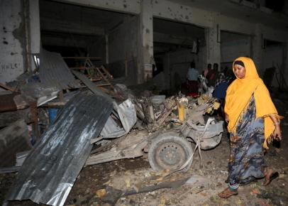 A Somali woman walks past the scene of a suicide car bomb attack near Juba hotel in capital Mogadishu August 22, 2015. At least 21 people were killed in two separate suicide car attacks in Somalia on Saturday, one in Mogadishu and another at a military training base in the southern port city of Kismayu, police and military sources said. REUTERS/Feisal Omar