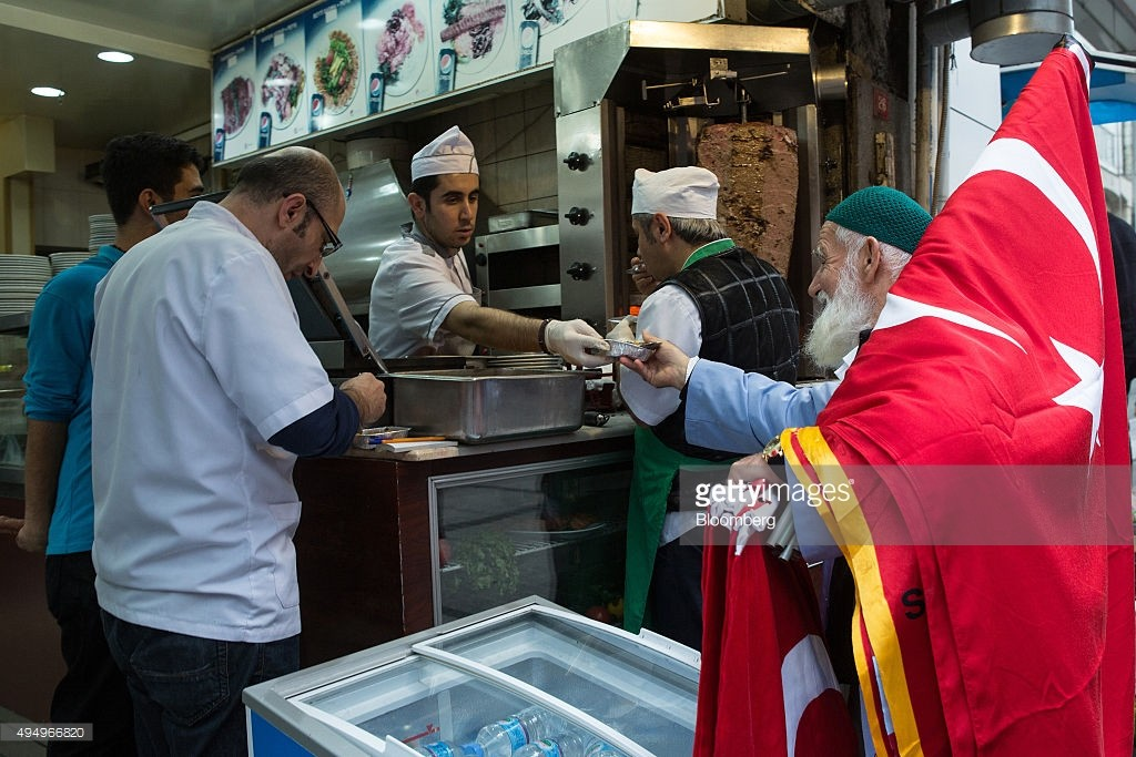 A man selling Turkish national flags stops to collect food from a kebab shop in Istanbul, Turkey, on Friday, Oct. 30, 2015. As Turks prepare to vote this weekend, some analysts see an increasing likelihood the five-month political deadlock that roiled markets is nearing an end. Photographer: Kerem Uzel/Bloomberg