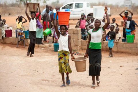 On 27 March, girls carry buckets filled with water, in the Kwanaya camp for internally displaced people, outside Yola, the capital of Adamawa, a state in the country's north-east. Other children, women and men are gathered nearby. UNICEF supports the operation of a small clinic and helps maintain a supply of fresh drinking water in the camp.  In March 2015 in Nigeria, 15.5 million people, including 7.3 million children, are affected by the continuing crisis in the country's north-eastern region. More than 1.2 million Nigerians have fled their homes as a result of violence and attacks by Boko Haram insurgents that have escalated since the beginning of 2015. Many of the displaced, most of whom are children and women, are sheltering with in host communities that have limited resources, and in formal and informal camps. All are in urgent need basic supplies, health and nutrition services, and critical water sanitation and hygiene support to prevent the spread of disease. Over 150,000 people – the vast majority children and women – have also fled to neighbouring Cameroon, Chad and Niger, further straining vulnerable communities – some of which are already facing food insecurity and malnutrition, are prone to disease outbreaks and natural disasters, and often already host hundreds of thousands of refugees, returnees and migrants who have escaped violence and hardship throughout the region. The impact of the crisis on children and women is of particular concern. Many of them have lost their homes and belongings –escaping with only the clothing they were wearing; and some have walked for days – or even weeks – to find refuge. Many children in the region have been traumatized and are in need of psychosocial support. They have witnessed violence and atrocities, including seeing parents and siblings slaughtered by Boko Haram insurgents; and have been exposed to or have experienced violence and brutality. Their homes have been burned and their schools have bee